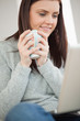 Smiling girl sitting on a sofa holding a cup of coffee and looki