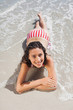Brunette lying down on beach