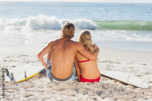 Rear view of a couple sitting on the beach and looking at the se