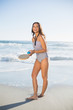 Smiling woman in one piece swimsuit playing with beach racket