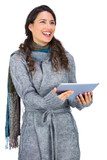 Happy brunette wearing winter clothes holding her tablet