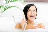 Lady lying in bathtub with suds plays with shower head