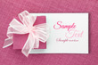 Pink gift box with ribbon on white card