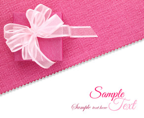 Gift box with ribbon on pink fabric texture isolated on white