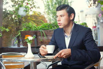 Guy with business suit and hairstyle  have rest in coffeehouse