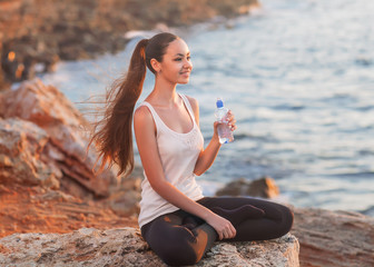 girl in lotus pose at sunset and holding water. Asian Caucasian