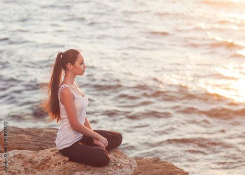 girl in lotus pose at sunset  - 55892622
