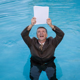 Senior man holding blank paperwork in water