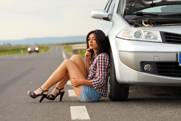Woman sitting on ground near broken car