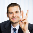 Businessman showing two fingers or victory gesture