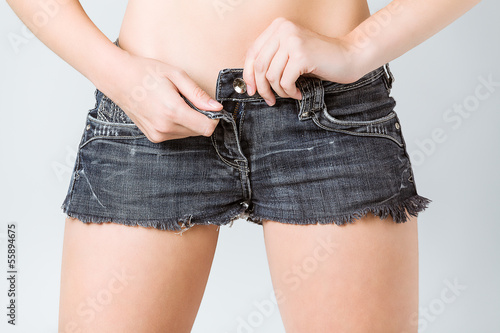 attractive girl undressing her jeans shorts