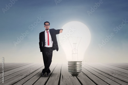 Businessman with lit bulb outdoor