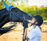 Young Woman Kissing a Black Stallion Horse