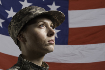 Young military woman pictured in front of US flag, horizontal