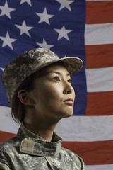 Military woman in front of US flag, vertical