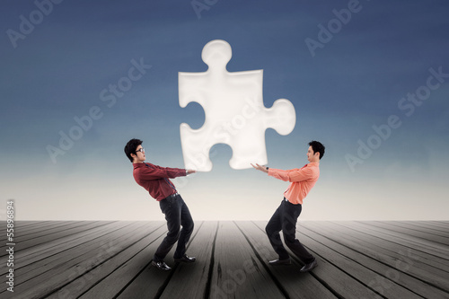 Two businessmen bring puzzle outdoor