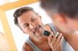 Handsome guy shaving in front of mirror
