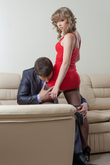 Businessman kissing pretty girl in erotic dress
