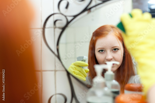 Teen girl  cleans mirror with sponge