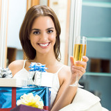 Cheerful woman with champagne and gifts