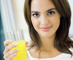 Cheerful young woman with orange juice at home