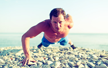 male athlete trains pushed on the nature on the beach