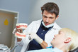Zahnarzt erklärt Patient Behandlung am Gebiss