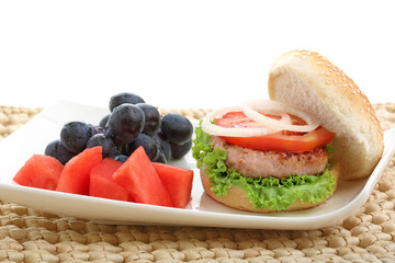 healthy low fat chicken burger with fruit isolated