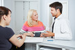 Arzt redet mit Patientin an Rezeption