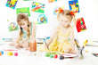Two kids, girls drawing with brush. Child creative development