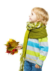 Child in green woolen scarf holding maple leaves