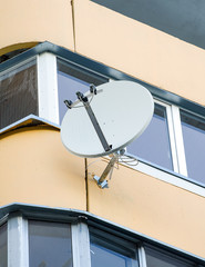 White sat TV dish on a balcony