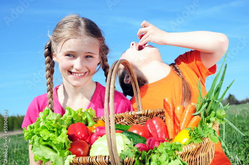 Two little girls with basket of vegetables