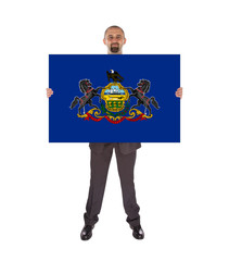 Smiling businessman holding a big card, flag of Pennsylvania