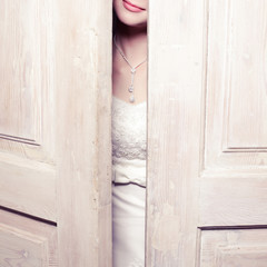 Beautiful bride's pink lips smiling behind white vintage wooden