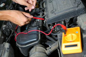 Auto mechanic uses multimeter voltmeter to check voltage level
