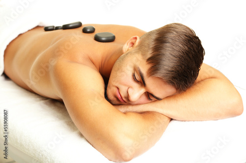Young man relaxing with hot stones on back before massage