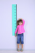 Little girl measuring height against wall in room