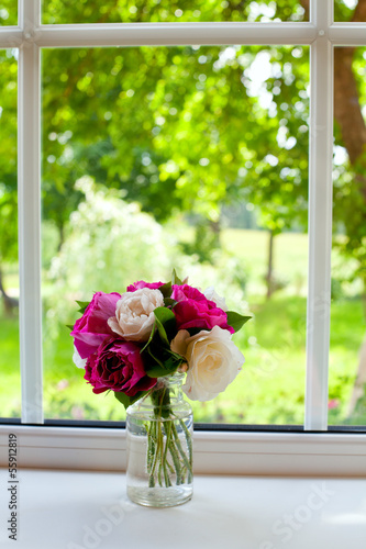 white and violet roses on window sill