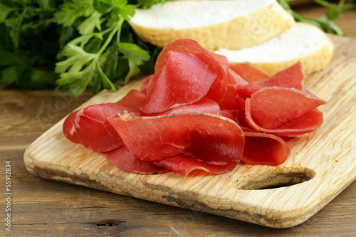 Papiers peints Snack Smoked meat bresaola on a cutting board