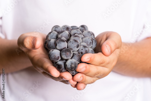 Child Holding a Bunch of Grapes
