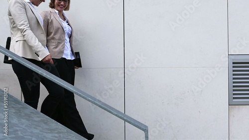 Two business woman walking down stairs