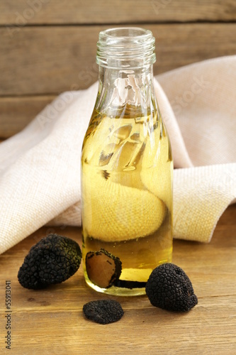 Olive oil flavored with black truffle on a wooden table