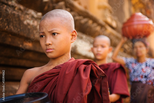 Southeast Asian young Buddhist monks walking morning alms