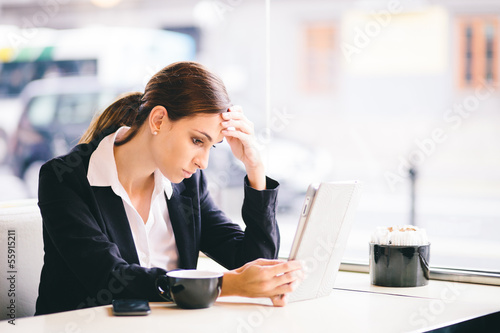 Tired and stressed businesswoman reading emails in cafe