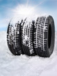 canvas print picture - Snowy winter tyres in front of blue sky with sunlights