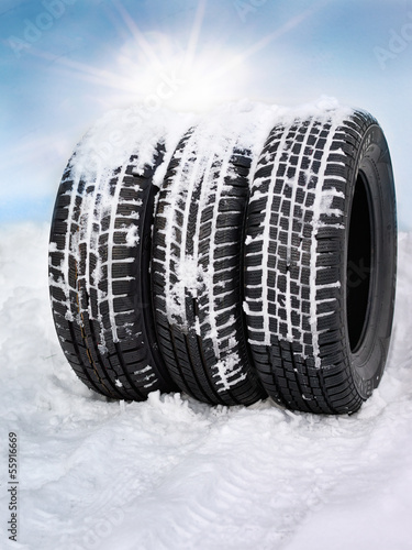 Snowy winter tyres in front of blue sky with sunlights