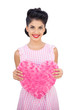 Delighted black hair model holding a pink heart shaped pillow