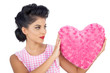 Charming black hair model holding a pink heart shaped pillow