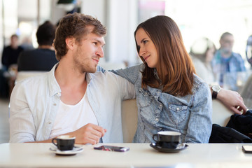 Young couple in lover staring at each other. In a coffee shop.